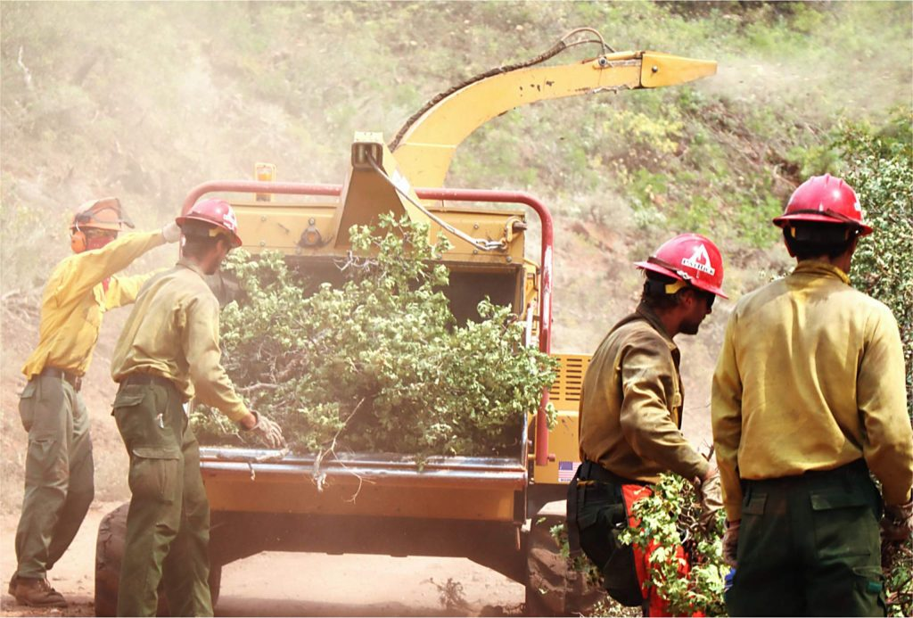 Firefighters mulch cleared brush to create defensible space on Lookout Mountain on Sunday. Such lines can help slow an otherwise rapidly growing fire and buy firefighters invaluable time to protect buildings and infrastructure.