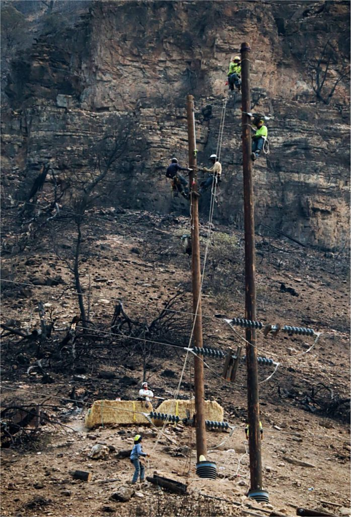 Linemen work to repair and replace damaged electrical poles through Glenwood Canyon on Sunday. More than 40 poles were damaged by the Grizzly Creek Fire.