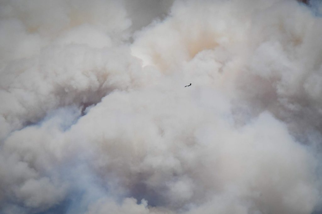 A spotter for an airtanker flies around the plume of smoke billowing from the Grizzly Creek Fire as it blows up in No Name Canyon on Wednesday afternoon.