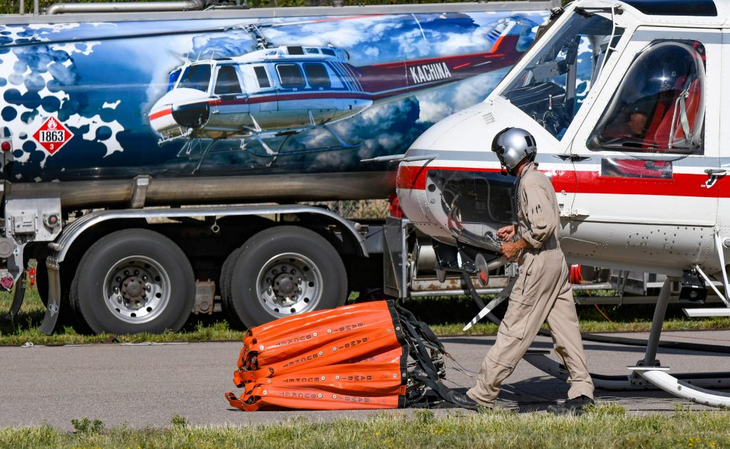 A Huey helicopter pilots walks to talk to other crewman after landing at the Glenwood Springs Municipal Airport to refuel before heading back to continue fighting the Grizzly Creek Fire on late Thursday afternoon.