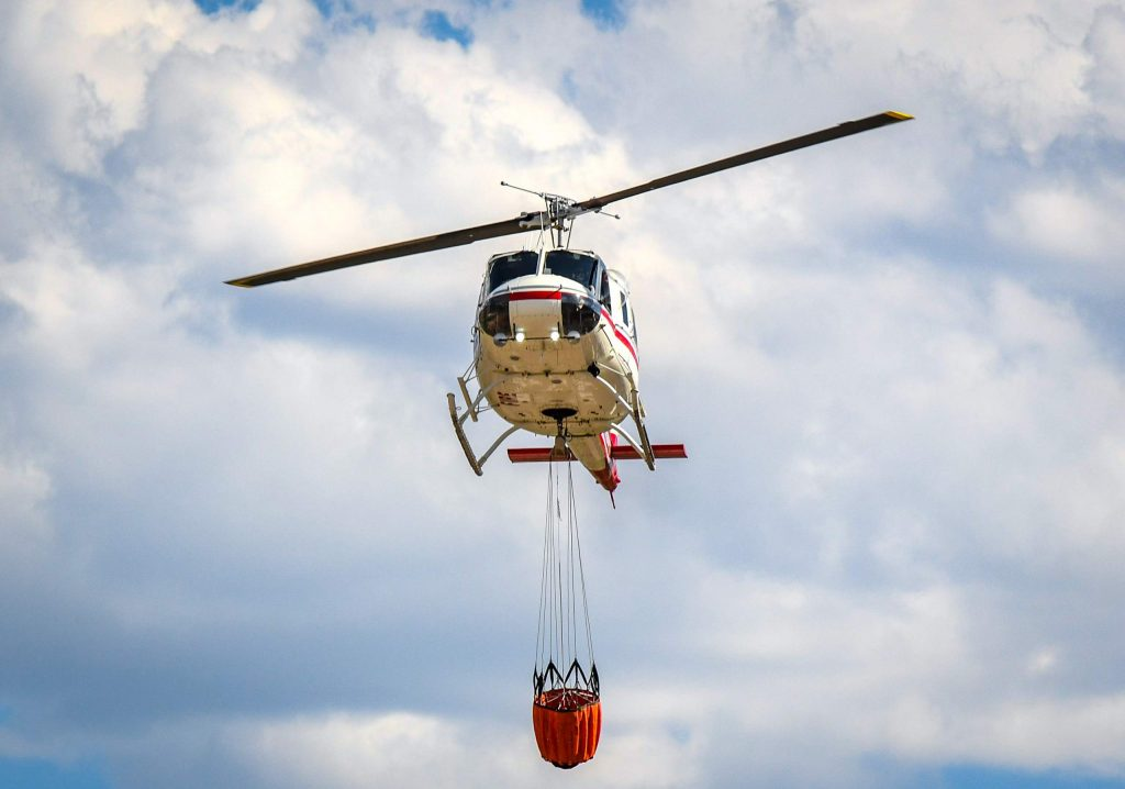 A Huey helicopter drops down to land at the Glenwood Springs Municipal Airport to refuel before returning to continue fighting the Grizzly Creek Fire late Thursday afternoon.