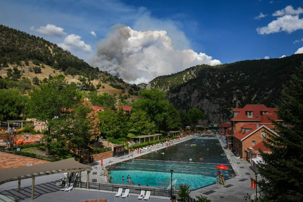 Smoke from the Grizzly Creek Fire billows behind the Glenwood Hot Springs Pool in Glenwood Canyon on August 13.