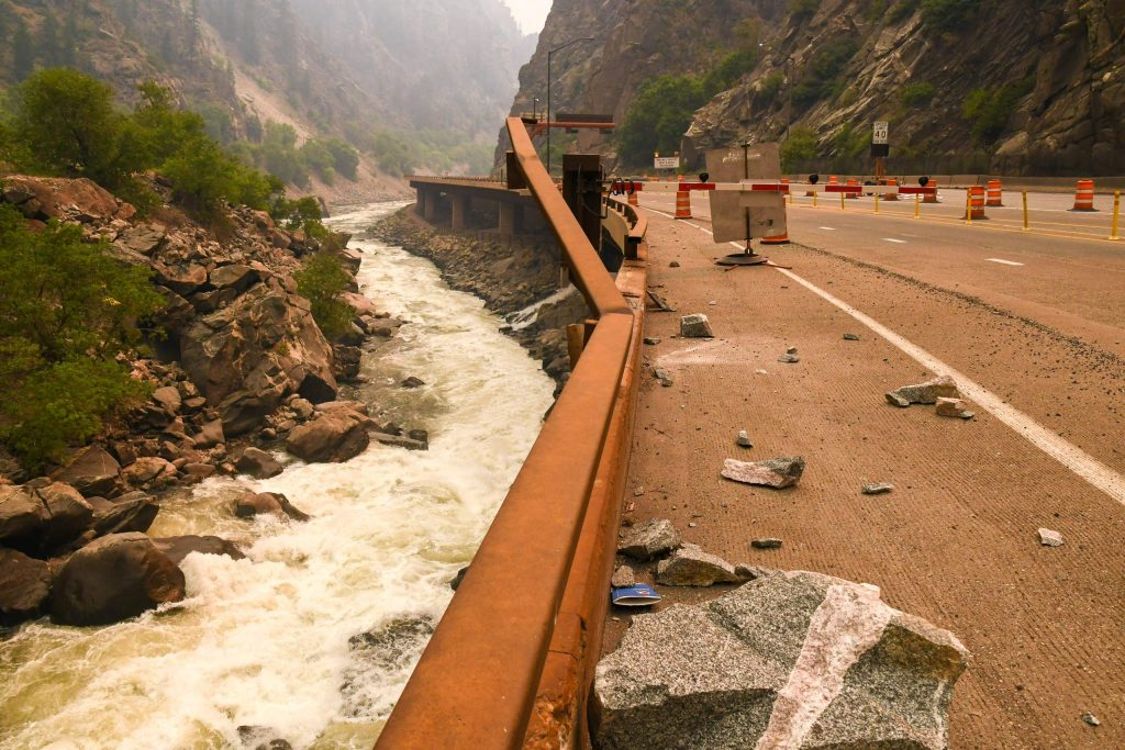 Damage to the guardrail is seen after boulders fell from the cliffs in Glenwood Canyon after the Grizzly Creek Fire swept through the canyon last week and continues to burn.