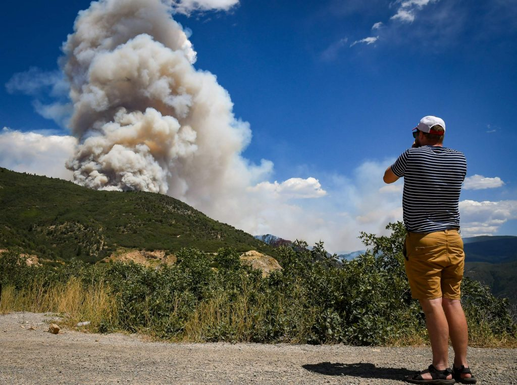 A man watches and takes photos of the Grizzly Creek Fire as it blows up in No Name Canyon on Tuesday afternoon after the fire initially started on Interstate 70 on Monday at MM 120.