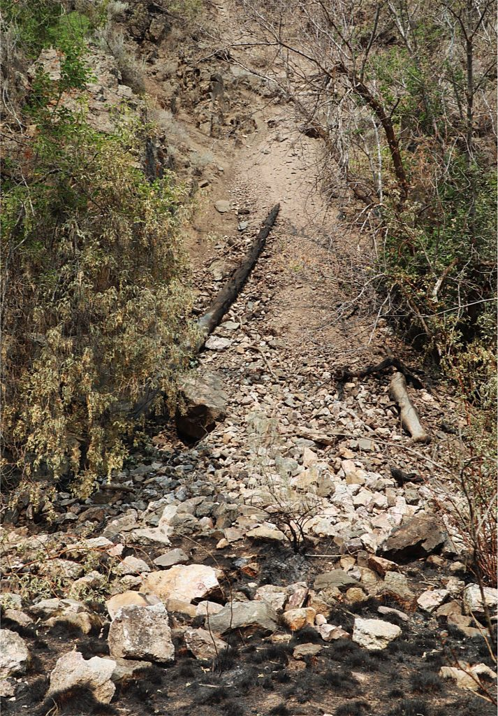 A debris slide near the concrete path leading to the Hanging Lake Trailhead. Loose rock, earth and timber are a safety concern in the area.