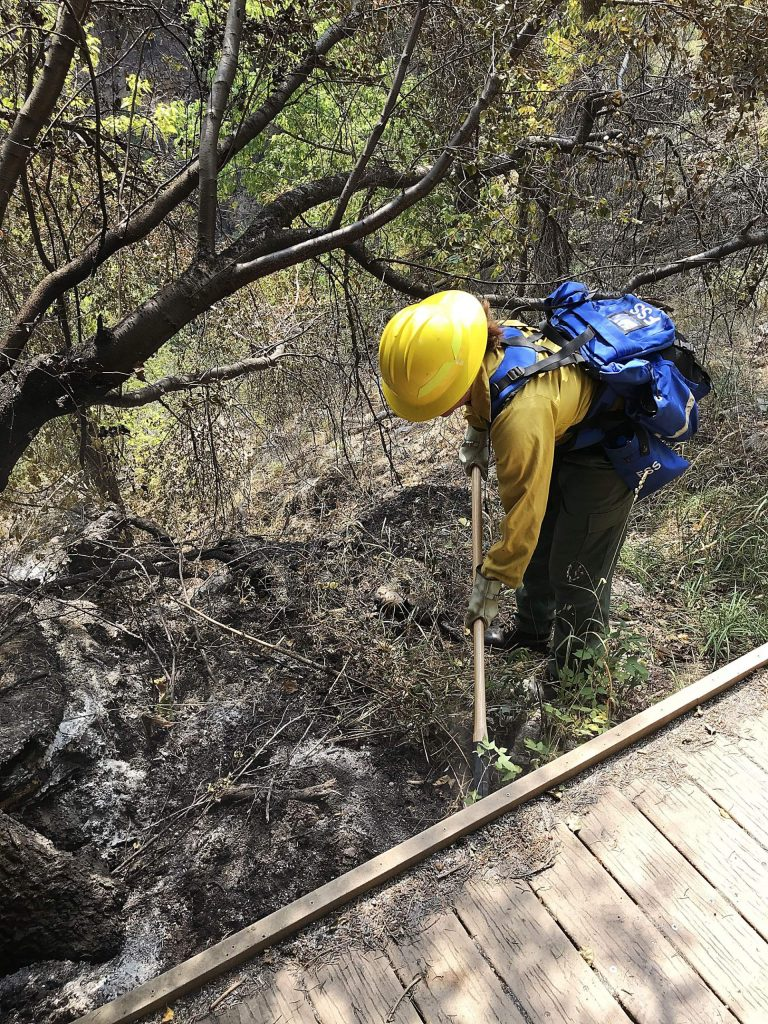A firefighter works on a burned area beneath the Hanging Lake boardwalk.