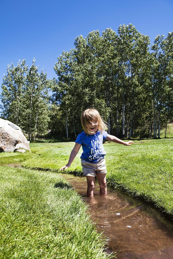 Robin Potts, 3, plays in the small stream at the Aspen Institute while visiting the park with her grandmother on Friday, August 7, 2020. (Kelsey Brunner/The Aspen Times)