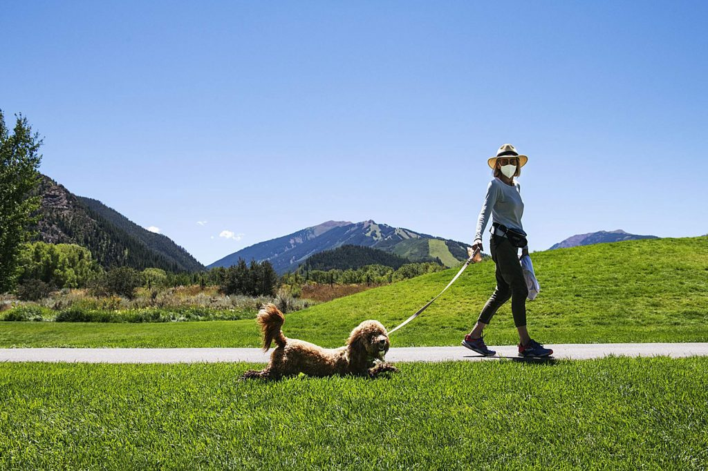 A woman watches as her dog scoots its belly across the grass at the Aspen Institute on Friday, August 7, 2020. (Kelsey Brunner/The Aspen Times)