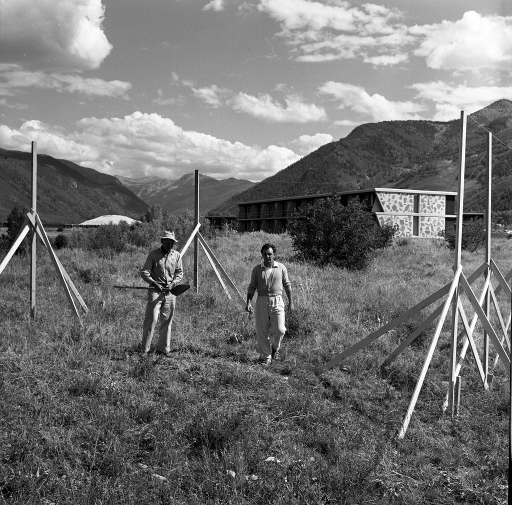 A black-and-white negative of the beginnings of construction of the Health Center at the Aspen Meadows, 1955. Two of the Meadows' residential buildings and the Music Tent (Saarinen) are visible in the background, as are Independence Pass and Aspen Mountain.