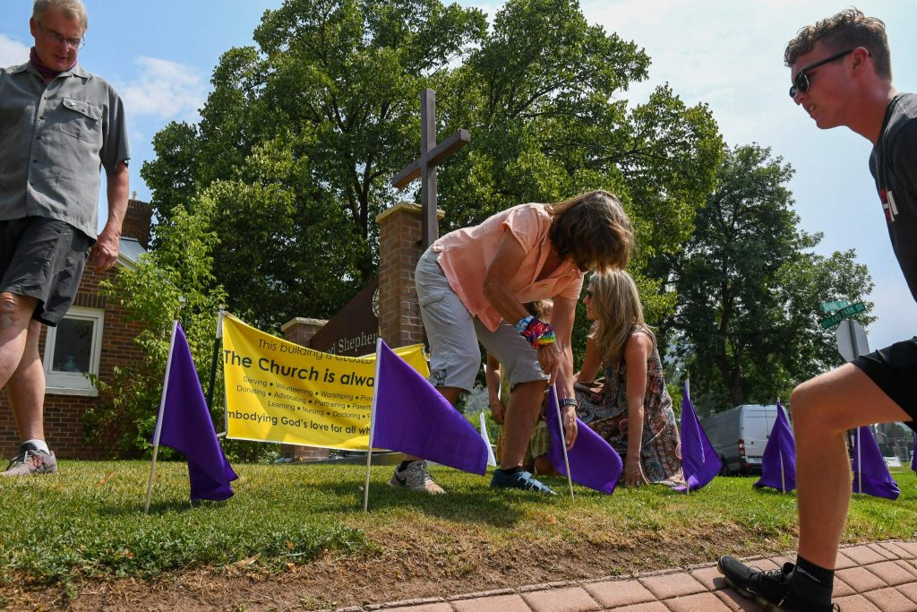 Gregg (left), Cath and AJ Adams place purple flags at the Good Shepherd Lutheran Church in Glenwood in recognition of National Overdose Awareness.