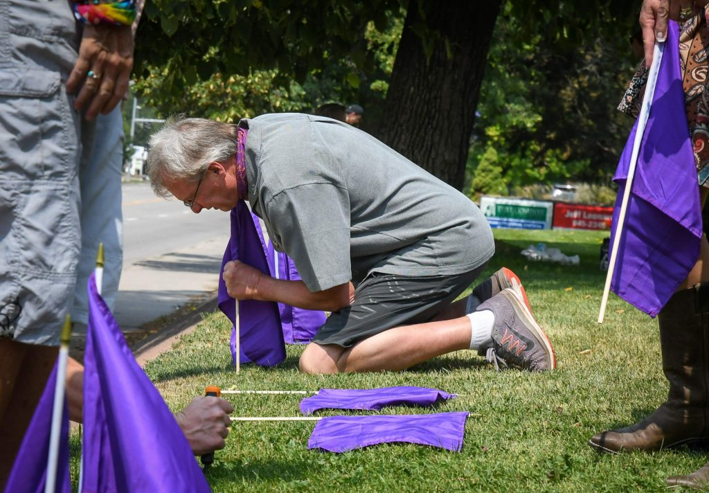 Gregg Adams places purple flags in recognition of National Overdose Awareness in honor of his daughter Emily with friends and family at the Good Shepherd Lutheran Church in Glenwood Springs.
