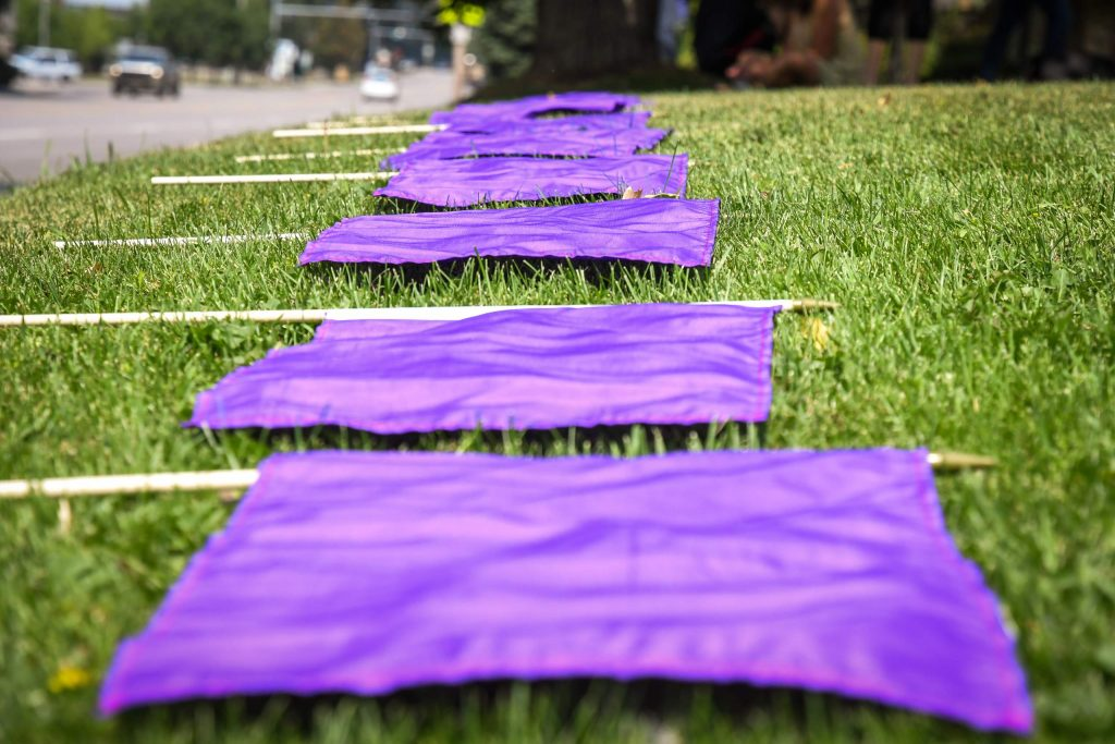 52 purple flags are laid out on the ground before being placed at the Good Shepherd Lutheran Church in Glenwood Springs to bring awareness to National Overdose Awareness.
