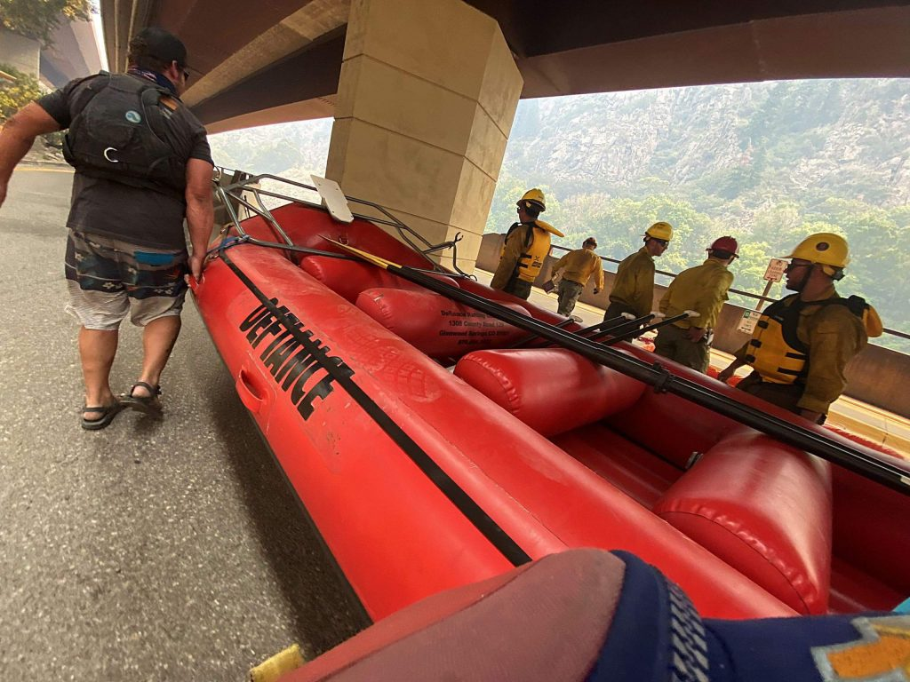 Defiance Rafting Company staffers work with firefighters at the Shoshone Ramp to unload boats for an attempt to ferry firefighters across the river on Tuesday. The mission was aborted, however, after it was determined it was too dangerous.