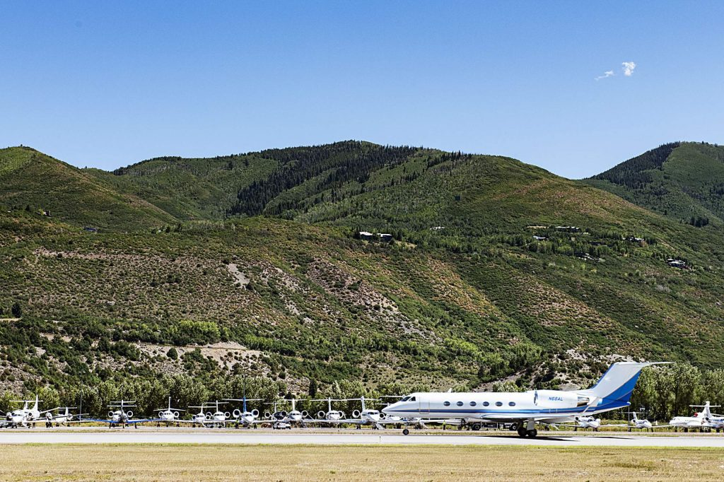 A private jet takes off Friday from Aspen/Pitkin County airport, with a large number of private planes parked behind it on the tarmac. The number of private flights into the airport was up more than 5% in June over June 2019. (Kelsey Brunner/The Aspen Times)