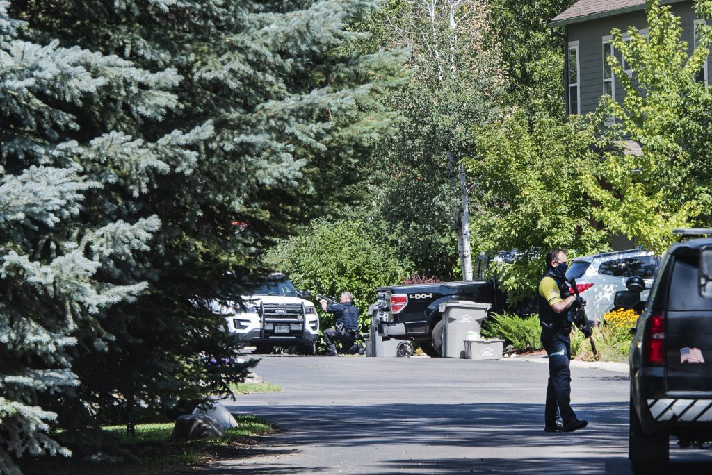 An officer crouches behind a police vehicle after using a speaker system to ask the last person in an Evans Court unit to come out of the house in Basalt on Thursday, August 27, 2020.