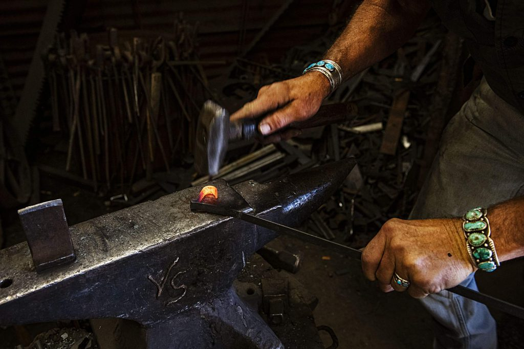 Vaughn Shafer folds a piece of hot metal into a heart shape in his Iron Arts Shop in El Jebel on Wednesday, August 12, 2020. (Kelsey Brunner/The Aspen Times)