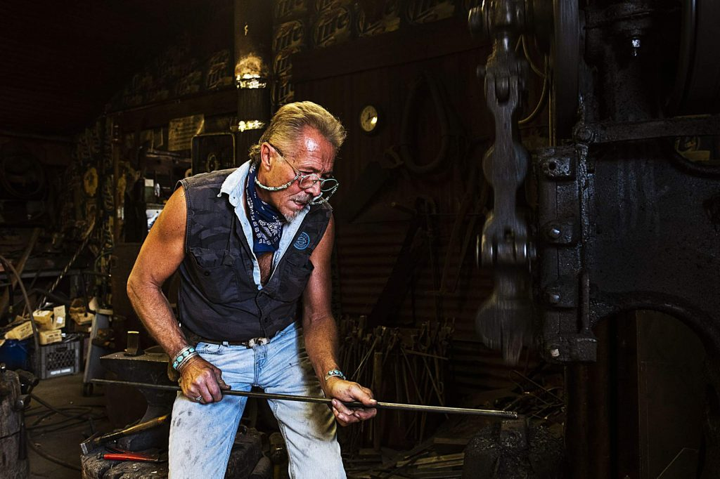 Vaughn Shafer uses a 100 year machine on a piece of metal in the Iron Arts Shop in El Jebel on Wednesday, August 12, 2020. (Kelsey Brunner/The Aspen Times)