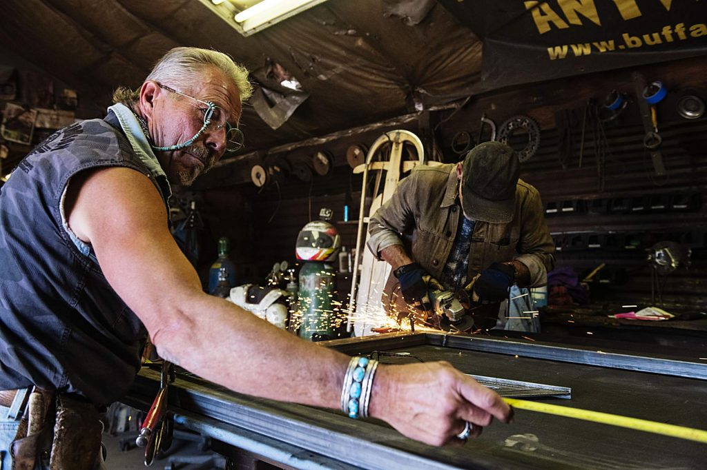 Vaughn Shafer, left, and Thomas Barlow work on a gate inside the Iron Arts Shop in El Jebel on Wednesday, August 12, 2020. (Kelsey Brunner/The Aspen Times)