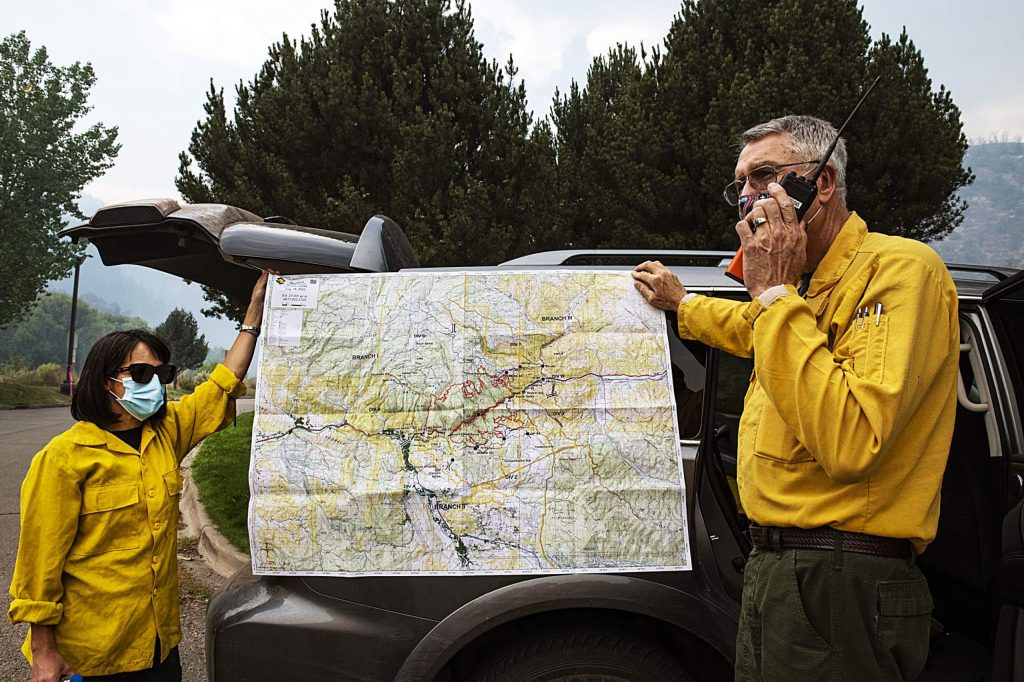 Wayne Patterson, right, talks in a walkie talkie while holding a perimeter map with Mina Bolton for the Grizzly Creek Fire on Thursday, August 20, 2020. (Kelsey Brunner/The Aspen Times)