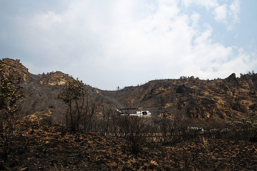 A helicopter takes off from I-70 among the scorched earth around the highway from the Grizzly Creek Fire outside of Glenwood Springs on Thursday, August 20, 2020. (Kelsey Brunner/The Aspen Times)