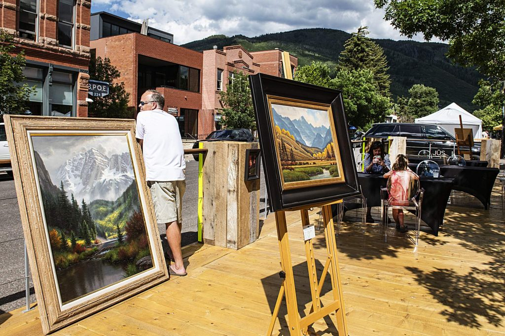 Paintings from the Wind River Gallery are displayed on a deck in the street in downtown Aspen on Tuesday, July 7, 2020.