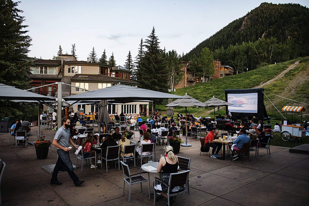 People watch Talladega Nights: The Ballad of Ricky Bobby from the lawn of Ajax Tavern at the base of Aspen Mountain on Friday, July 10, 2020. Movies will be held at Ajax Tavern every Friday through August 21. There is patio and lawn seating available.