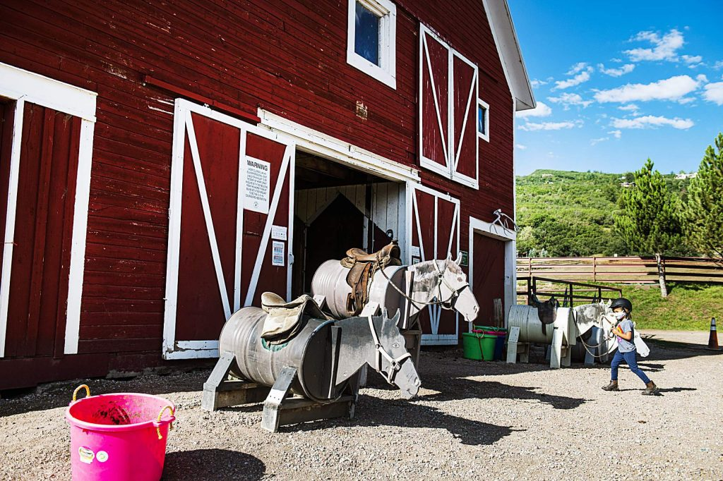 A young rider walks into the Cozy Point Ranch barn in Aspen on Wednesday, July 29, 2020.