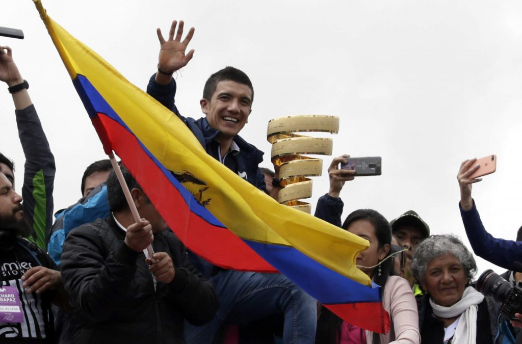 People welcome Ecuadorian cyclist Richard Carapaz, center with trophy, after his win in the