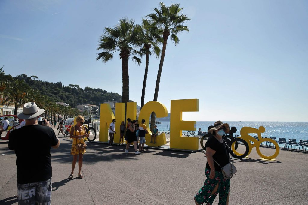 People walk next to an installation set up for the start of the 107th Tour de France cycling race, in Nice, southern France, Thursday, Aug. 27, 2020. The Tour de France sets off shrouded in uncertainty and riding in the face of the coronavirus pandemic and mounting infections in France.