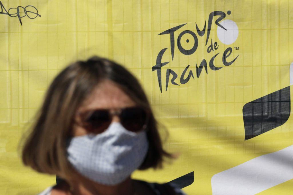 A woman wears a face mask as she walks past a Tour de France logo, in Nice, southern France, Thursday, Aug. 27, 2020. The Tour de France sets off shrouded in uncertainty and riding in the face of the coronavirus pandemic and mounting infections in France.