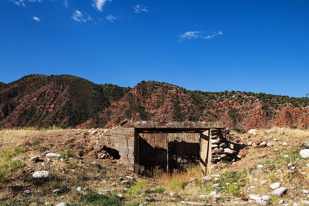The mountains rise behind a collapsed potato cellar in Glassier Open Space in Basalt on Thursday, August 6, 2020. (Kelsey Brunner/The Aspen Times)