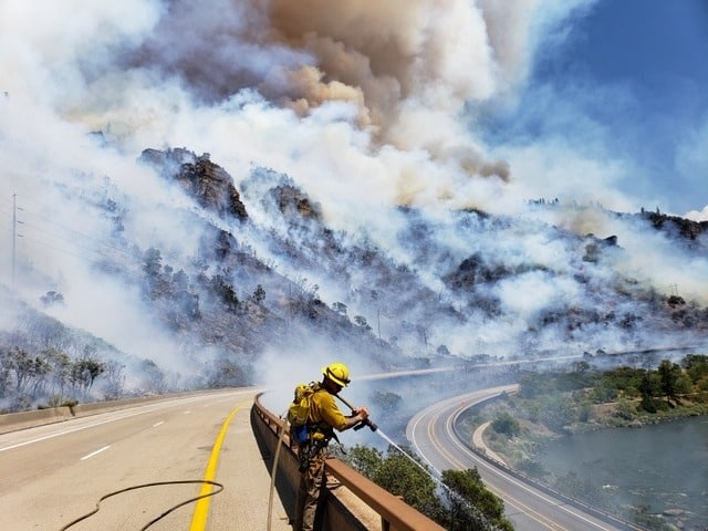 Fire crews stand on westbound Interstate 70 in Glenwood Canyon on Monday as they fight the Grizzly Creek Fire.