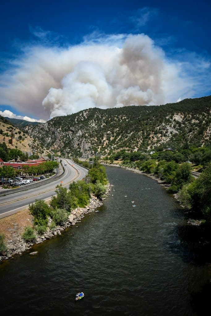 People float down the Colorado River as smoke billows from the Grizzly Creek Fire in Glenwood Canyon on Monday afternoon.