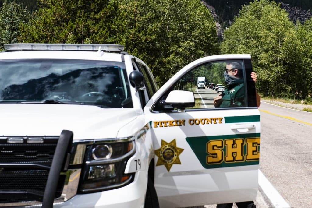 Pitkin County deputy Ryan Voss turns his vehicle's lights on to pull over an oversized semi-truck at the entrance of Independence Pass on Tuesday, August 11, 2020.