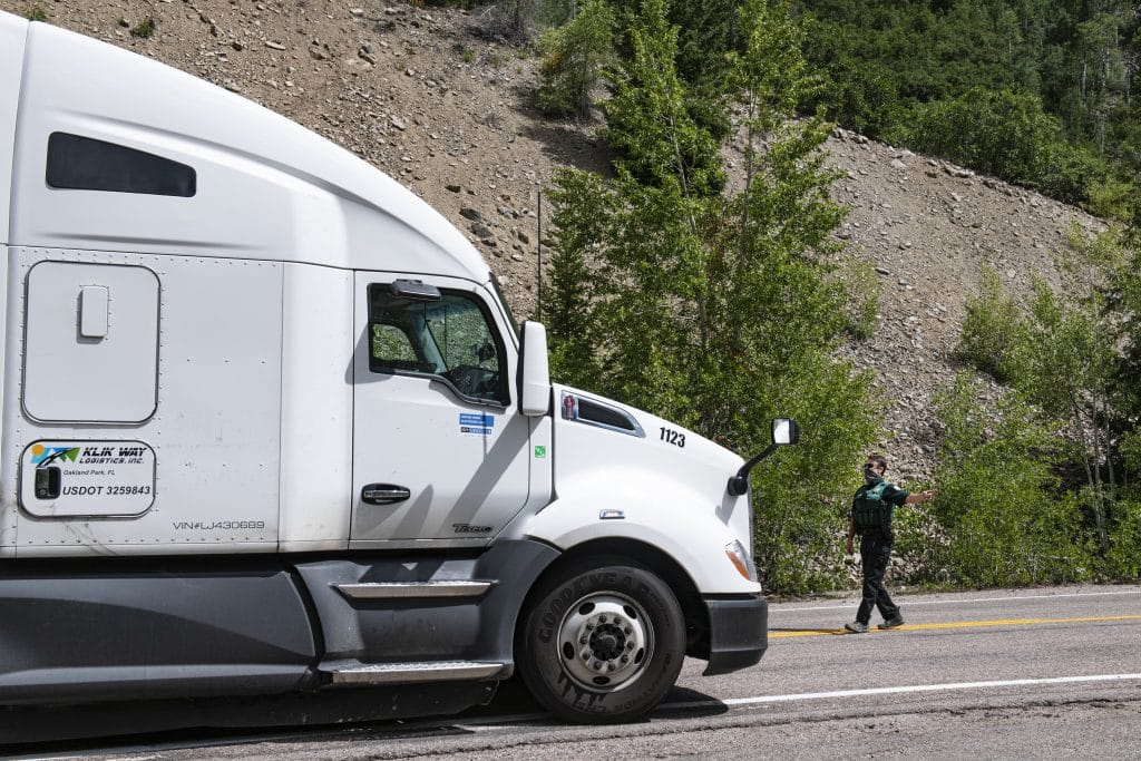 Pitkin County deputy Ryan Voss directs a semi to pull over in the oversized vehicle turnaround at the entrance of Independence Pass on Tuesday, August 11, 2020.