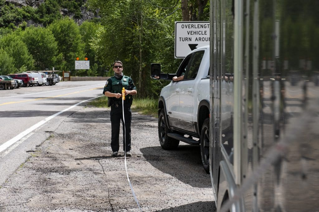 Pitkin County deputy Ryan Voss measures a truck and trailer at the oversized vehicle turnaround at the entrance to Independence Pass on Tuesday, August 11, 2020.