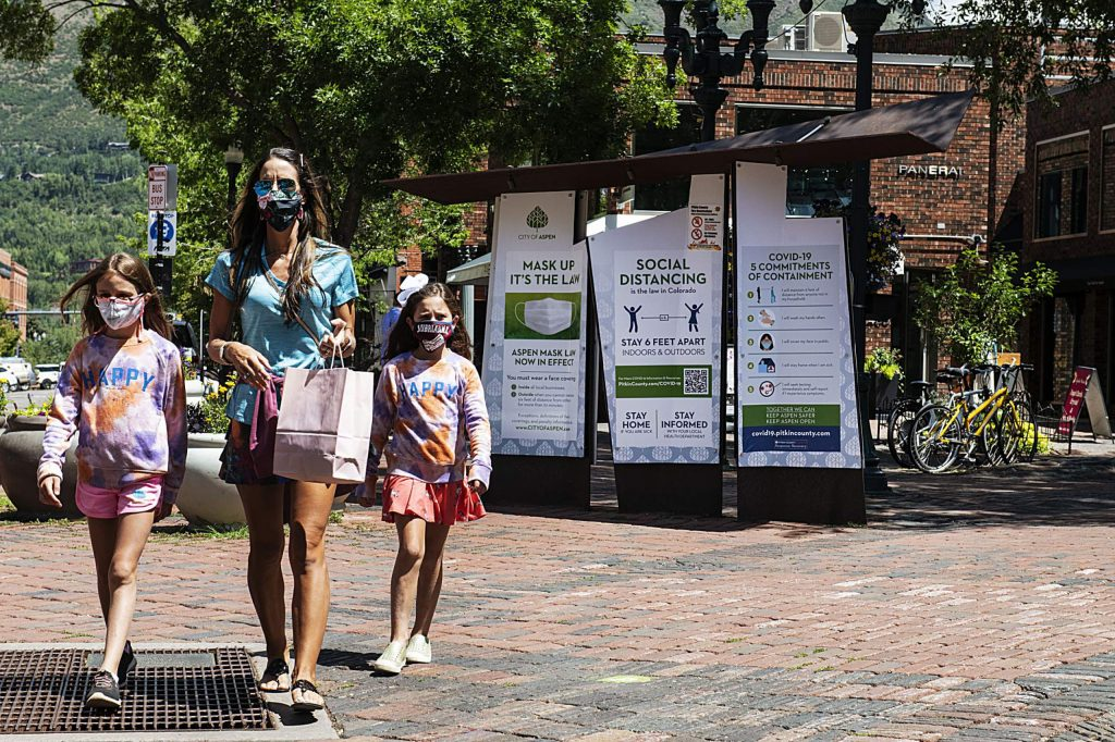 Elliot Mitchell, 9, left, Dina Diehl, and Aubrianna Diehl, 8, wear masks while walking through Aspen's downtown core on Thursday, July 30, 2020. (Kelsey Brunner/The Aspen Times)