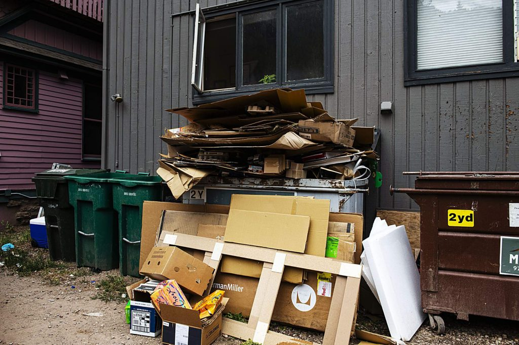 Cardboard spills out of Alpine Property Management's recycling container behind a building on Main Streeet in Aspen on Thursday, August 6, 2020. (Kelsey Brunner/The Aspen Times)