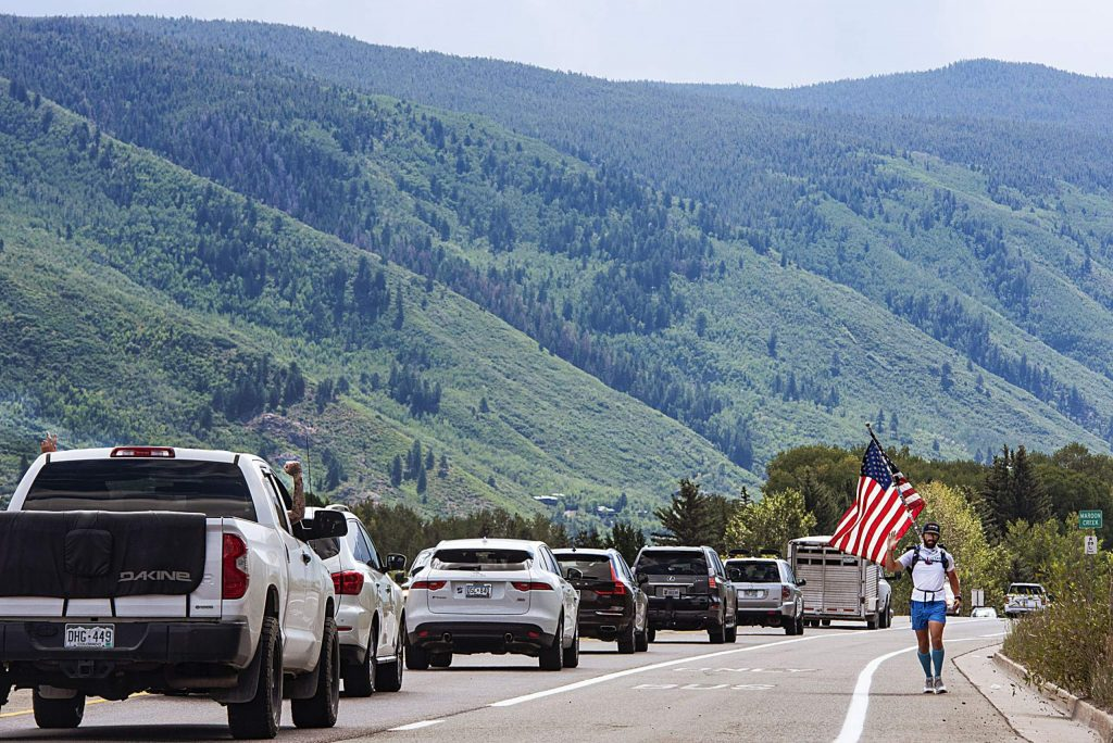 """Russell Larkins, 30, also known as Run Russell Run, jogs near Maroon Creek Bridge toward Glenwood Springs and waves at passersby during his across country journey on Wednesday, Aug. 12, 2020, in Aspen. Larkins is running from Wilmington, North Carolina, to San Francisco, California, to raise awareness for veteran suicide and money for veterans that are struggling financially. He began his run on April 27 and plans to finish in the next six weeks. Larkins was an infantry squad leader in the Marine Corps in Afghanistan. He was diagnosed with Post Traumatic Stress Disorder when he returned and found that exercise, meditation and yoga helped him. Part of his mission is to motivate veterans to get outside and exercise, especially during the pandemic. Larkins expressed that the continental divide and Independence Pass was by far the hardest and most beautiful part of his trip thus far. """"It was 32 miles of pain and 32 miles of beauty,"""" Larkins said. (Kelsey Brunner/The Aspen Times)"""