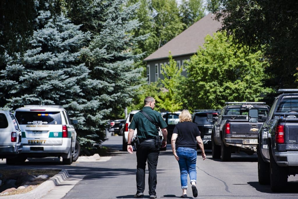 Pitkin County Officer Alex Burchetta walks with the owner of the unit at the scene of a disturbance on Evans Court in Basalt on Thursday, August 27, 2020. The woman, whose identity was confirmed by an official on scene, is also the mother of one of the men taken into custody.
