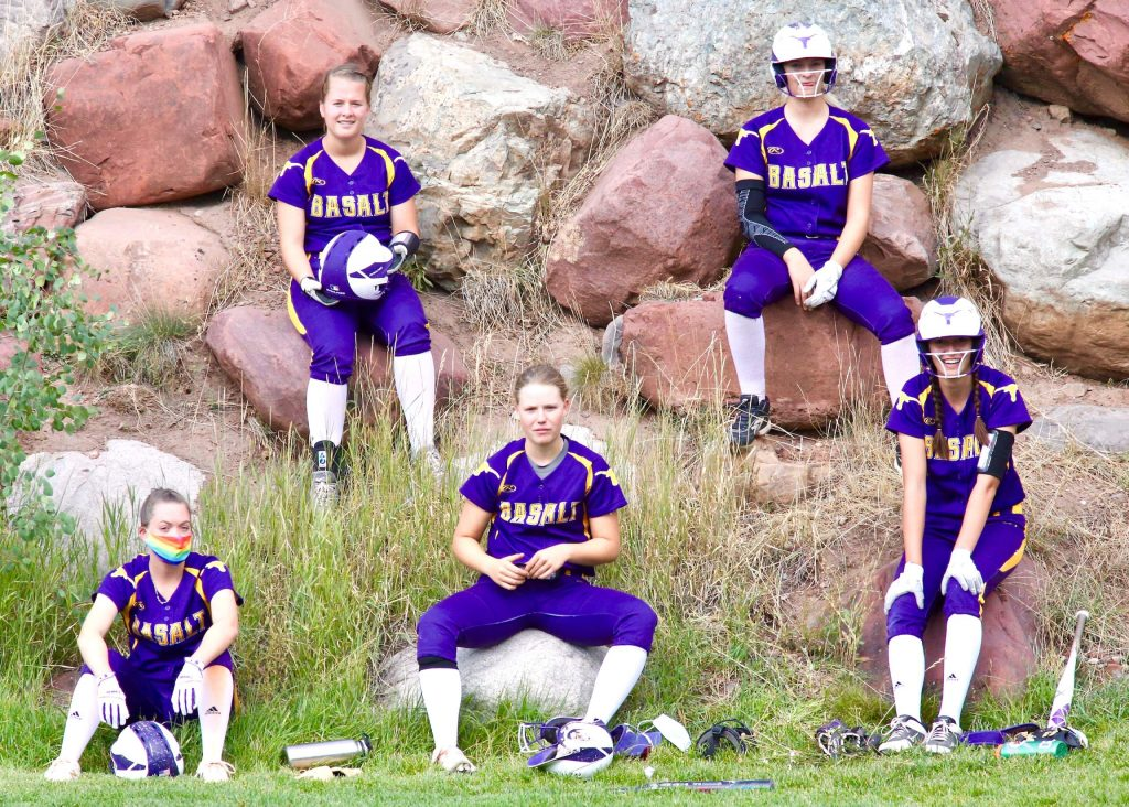Members of the Basalt High School softball team hang out on the rocks during their season-opening game against Aspen on Tuesday, Aug. 25, 2020, at Upper Moore Field. Because of the coronavirus pandemic, various safety measures have been put in place for the season, one of them being that players aren't allowed to use dugouts, leading the Longhorns to find a non-traditional spot to sit. (Photo by Austin Colbert/The Aspen Times)