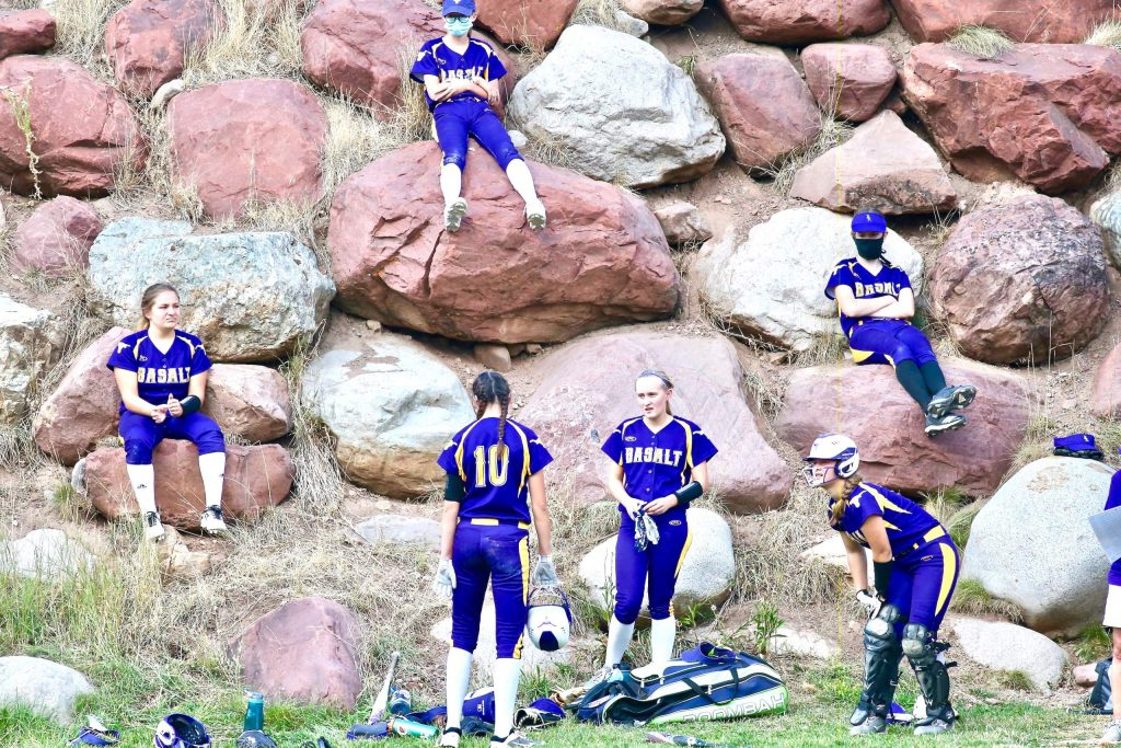 Members of the Basalt High School softball team hang out on the rocks during their game against Aspen on Tuesday, Aug. 25, 2020, at Upper Moore Field. Because of the coronavirus pandemic, various safety measures have been put in place for the season, one of them being that players aren't allowed to use dugouts, leading the Longhorns to find a non-traditional spot to sit. (Photo by Austin Colbert/The Aspen Times)