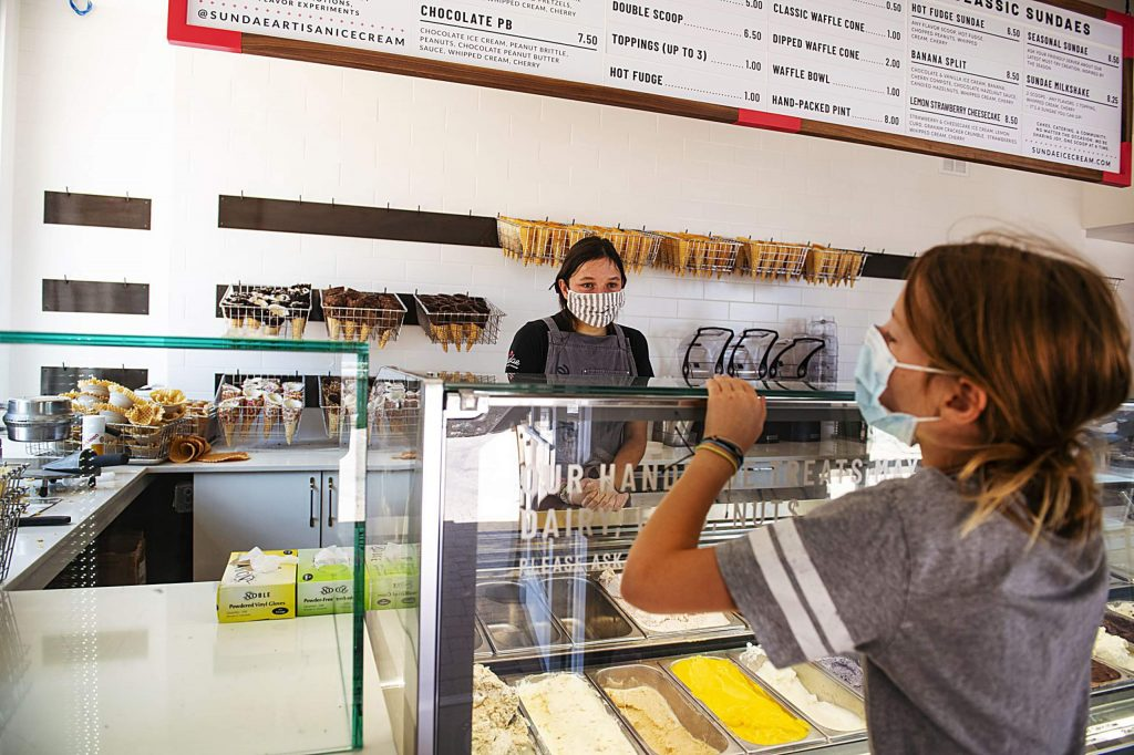 Sundae's Annika Bucchin, 17, helps a young customer with a waffle cone selection at the artisan ice cream shop in Snowmass Base Village on Thursday, July 30, 2020.
