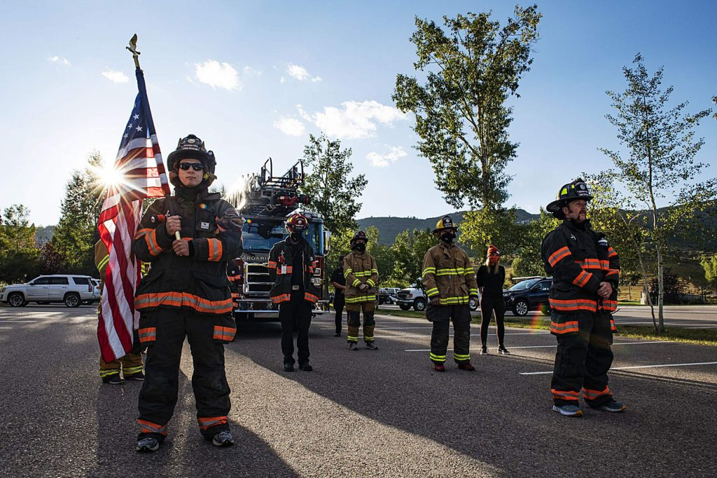 Local firefighters stand for a moment of silence during the fifth annual Axes and Arms 9/11 climb starting in Town Park on Friday, Sept. 11, 2020. (Kelsey Brunner/The Aspen Times)