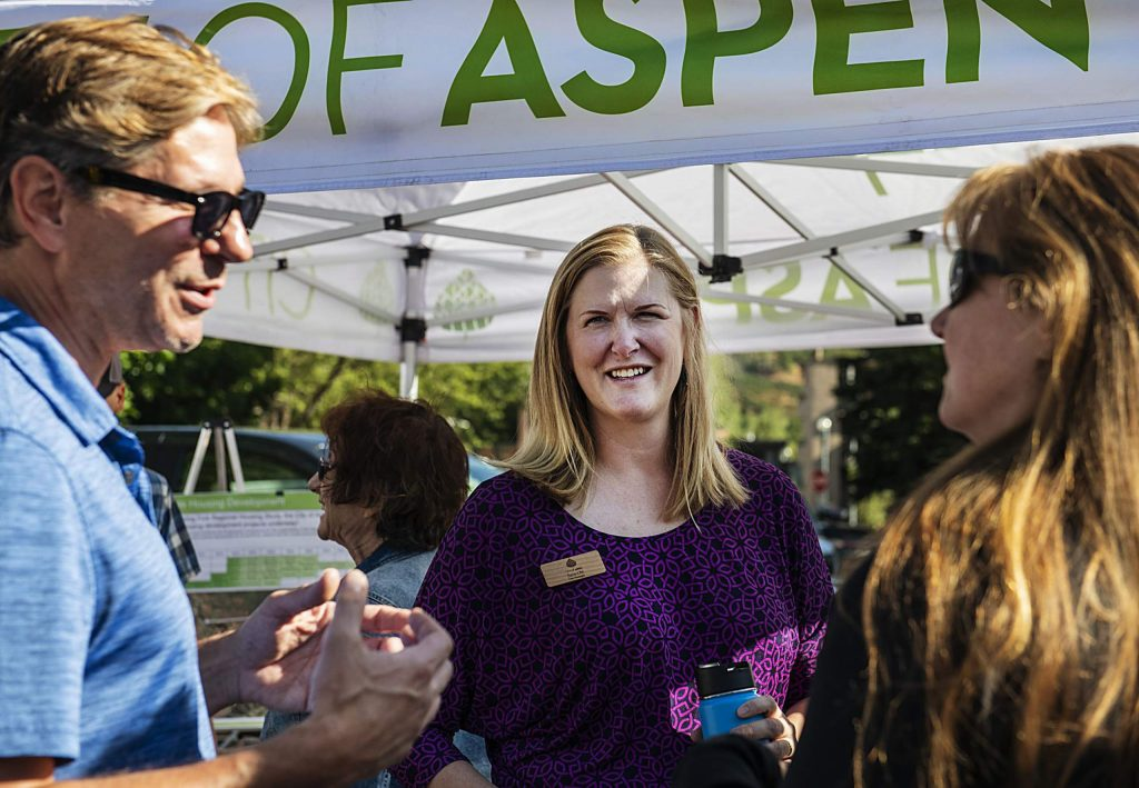 Aspen City Manager Sara Ott, center, listens as Chris Everson, left, and Amy Mountjoy talk about affordable housing projects at the farmer's market on Saturday, Sept. 7, 2019. (Kelsey Brunner/The Aspen Times)