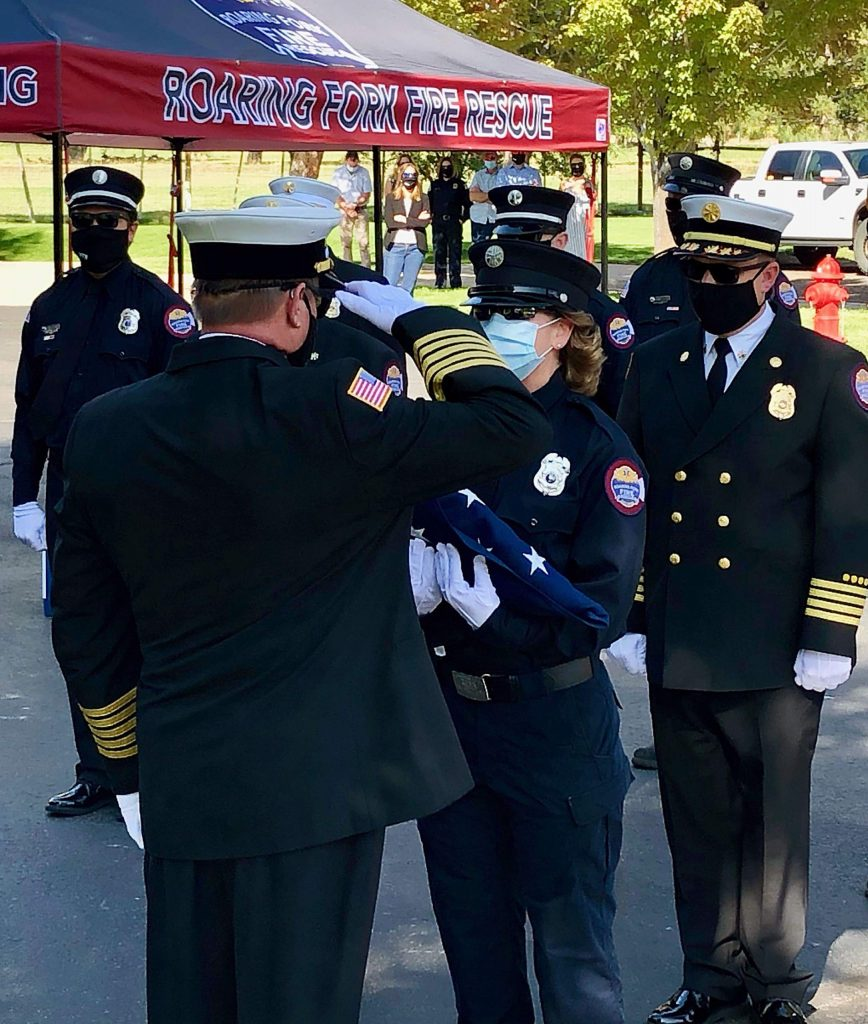 Roaring Fork Fire Rescue Fire Chief Scott Thompson salutes retiring firefighter and paramedic Christine Benton after presenting her with the American flag.