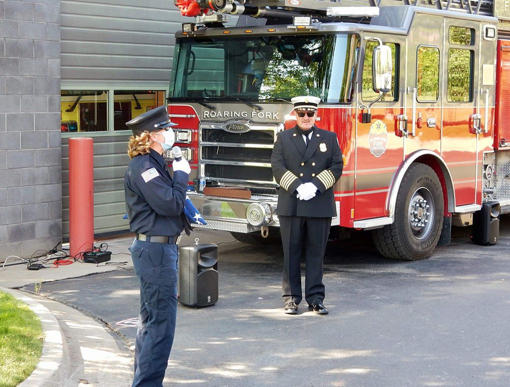 Retiring firefighter and paramedic Christine Benton (left) speaks at her retirement ceremony Friday, Sept. 25 as Fire Chief Scott Thompson looks on.