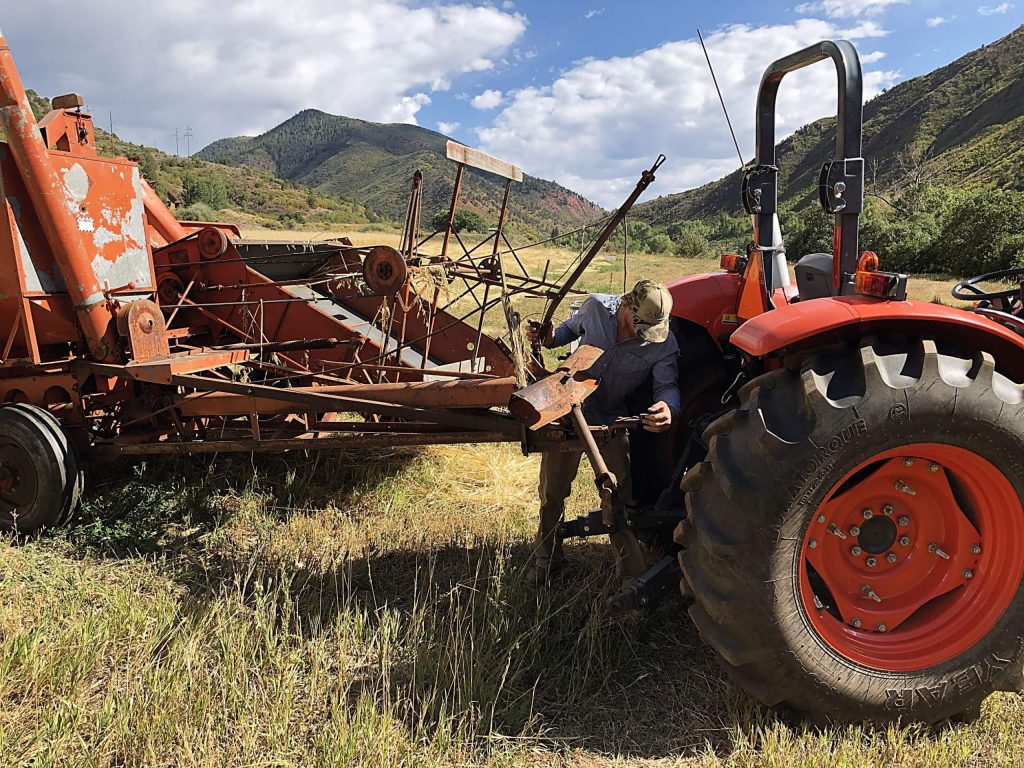 Cooper Means hooks up an Allis Chalmers All Crop Harvester to a tractor to prepare to harvest a small field of oats in Old Snowmass.