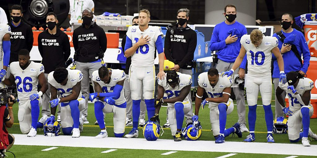 Los Angeles Rams kneel next to quarterback quarterback Jared Goff (16) during the National Anthem prior to a NFL football game against the Dallas Cowboys on opening night at SoFi Stadium in Inglewood on Sunday, September 13, 2020. (Keith Birmingham/The Orange County Register via AP)