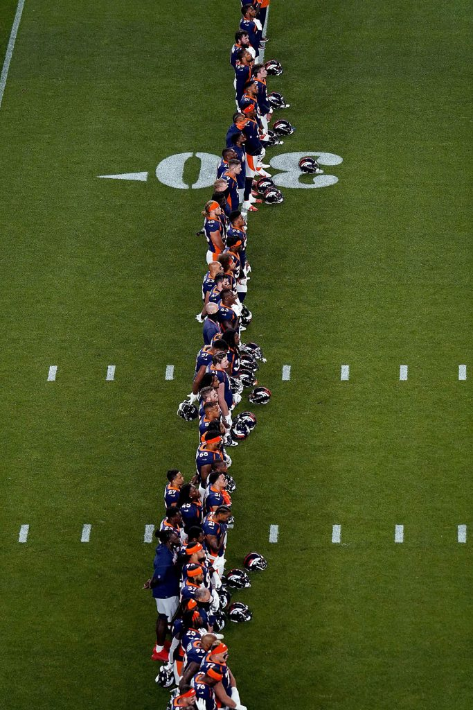 The Denver Broncos stand during a rendition of